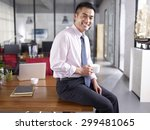 An Asian Businessman Holding...