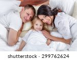 happy family lying on a bed... | Shutterstock . vector #299762624