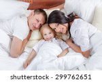 happy family lying on a bed... | Shutterstock . vector #299762651