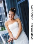 Small photo of Fabulous bride is standing near the window. She's looking jilt and smiling.