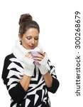 Small photo of Cold attractive stylish woman in an elegant black and white winter outfit clasping a mug of hot coffee in her hands while savoring the aroma with a look of anticipation