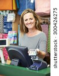 Small photo of Female Cashier At Sales Desk With Credit Card Machine