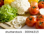 Fresh greens and vegetables: green salad, cauliflower, onion, tomato, sweet pepper - stock photo