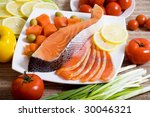 Fresh salmon on a plate with sliced lemon and fresh vegetables - stock photo