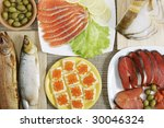 Assorted fishes, open sandwich with red caviar, olives, lemon, greens - stock photo