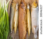 Assorted smoked fishes on a table with green onion - stock photo