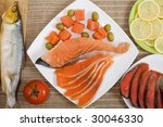 Different kinds of fish with sliced lemon, olives and tomato - stock photo