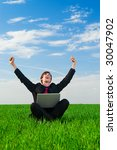 happy businessman with laptop sitting at the grass - stock photo