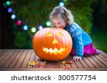 Little Girl Carving Pumpkin At...