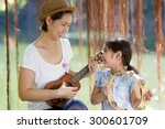 asian daughter playing ukulele... | Shutterstock . vector #300601709