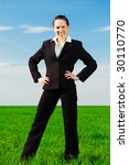 successful businesswoman standing at the green grass - stock photo
