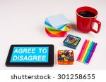 Small photo of Business Term / Business Phrase on Tablet PC - Colorful Rainbow Colors, Cup, Notepad, Pens, Paper Clips, White surface - White Word(s) on a cyan background - Agree To Disagree
