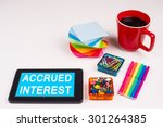 Small photo of Business Term / Business Phrase on Tablet PC - Colorful Rainbow Colors, Cup, Notepad, Pens, Paper Clips, White surface - White Word(s) on a cyan background - Accrued Interest