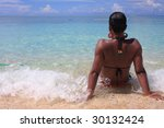 Lady sitting in shallow ocean water - stock photo