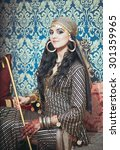 Small photo of Portrait of a beautiful woman in oriental dress. Grace and beauty.Young girl in Egyptian garb