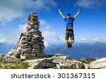 Man jumping out of joy beside a large cairn on a mountaintop.