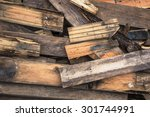 Small photo of Photograph of old, rotten, scrapped floorboards and decking planks amassed and scattered in a untidy heap.