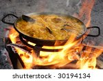 Preparing paella on the traditional way with all kinds of sea food - stock photo