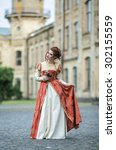 Small photo of Beautiful girl in a beautiful old dress like a princess or a fairy castle in the background