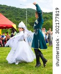 "Small photo of DAKHOVSKY, RUSSIA - JULY 25 2015: The boy and the girl in beautiful national suits dance traditional Adyghe dance. The Festival ""Lago-Naki: Kunatskaya"" was held in the mountains of Adygea in Dakhovsky"