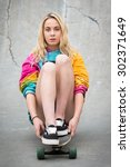 Small photo of Pretty bond girl sitting on skateboard