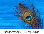A Peacock Feather On Wooden...