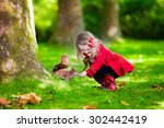 Girl Feeding Squirrel In Autum...