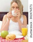 pretty woman having breakfast... | Shutterstock . vector #302476571