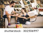 young couple sitting on a couch ...   Shutterstock . vector #302506997