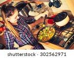 Woman In Kitchen Cooking Stir...