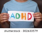 Small photo of Young boy holds ADHD text written on sheet of paper. ADHD is Attention deficit hyperactivity disorder. Close up.
