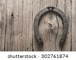 Stock photo new metal horseshoe on old retro vintage aged wooden background empty space for inscription or 302761874