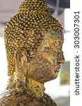 Small photo of Closeup Buddha's head with gold foil worship paper at Bung Thong Lang Temple