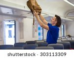young man putting luggage into... | Shutterstock . vector #303113309