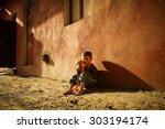 Stock photo alone sad child playing on a street 303194174