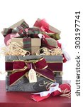 Small photo of Large Christmas gift hamper with traditional red and green wrapping on red wood table.