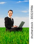 smiley woman with computer sitting at the green meadow - stock photo