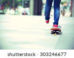 young skateboarder legs riding... | Shutterstock . vector #303246677