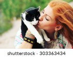 Stock photo young happy smiling red haired girl dressed in hippie bohemian style hugging cat outdoors 303363434
