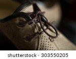 lacing men's summer shoes on... | Shutterstock . vector #303550205