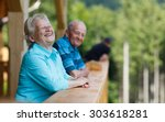 Happy senior couple looking to surroundings areas and smiling. Posing in wooden tower and watching for nature scenery in forest. Summer holidays. Blurred forest background.