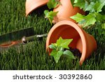 Clay flower pots on grass with ivy plant and gardening spade in background.  Close-up with shallow dof. - stock photo