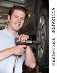 Small photo of Mechanic In Garage Using Air Hammer On Car Wheel
