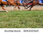 Stock photo horses running past on the racetrack 304333565