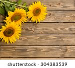 Постер, плакат: Three sunflowers are on