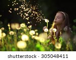 Girl Blowing A Dandelion Seeds...