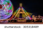 Small photo of Giant Ferris Wheel and swing boat amusement ride side by side in night time shot with long exposure.