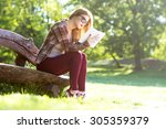 young woman sitting on a bench... | Shutterstock . vector #305359379