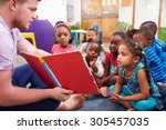 volunteer teacher reading to a... | Shutterstock . vector #305457035