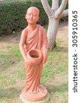 Buddhist novice holding alms bowl clay doll at Thai Buddhist temple - stock photo